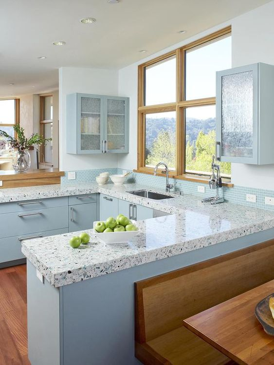 a chic blue kitchen with a blue tile backsplash and a pretty terrazzo countertop includes a view and looks wow