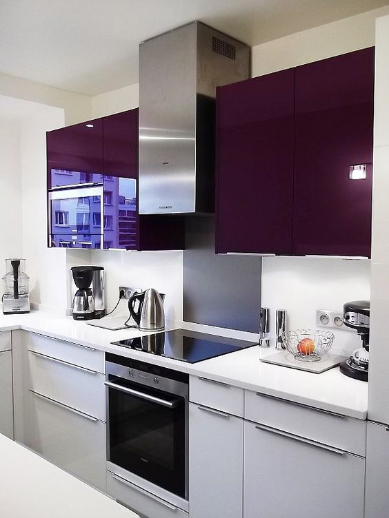 a chic contemporary kitchen in deep purple and grey, with a white backsplash and countertop looks jaw-dropping