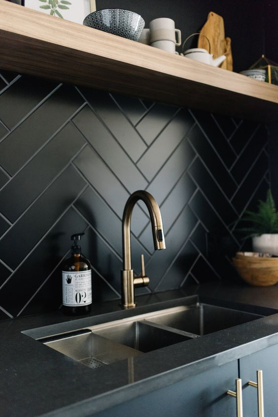 a chic dark kitchen with a matte black herringbone backsplash, black coutnertops, a floating shelf and brass touches