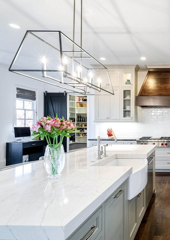 a chic dove grey kitchen with white quartz countertops and a white tile backsplash, a wooden hood and a lovely pendant lamp