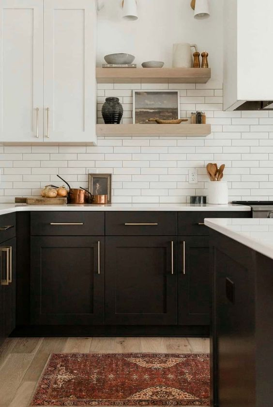 a chic farmhouse kitchen with black and white cabinets, a white tile backsplash and white quartz countertops and floating shelves