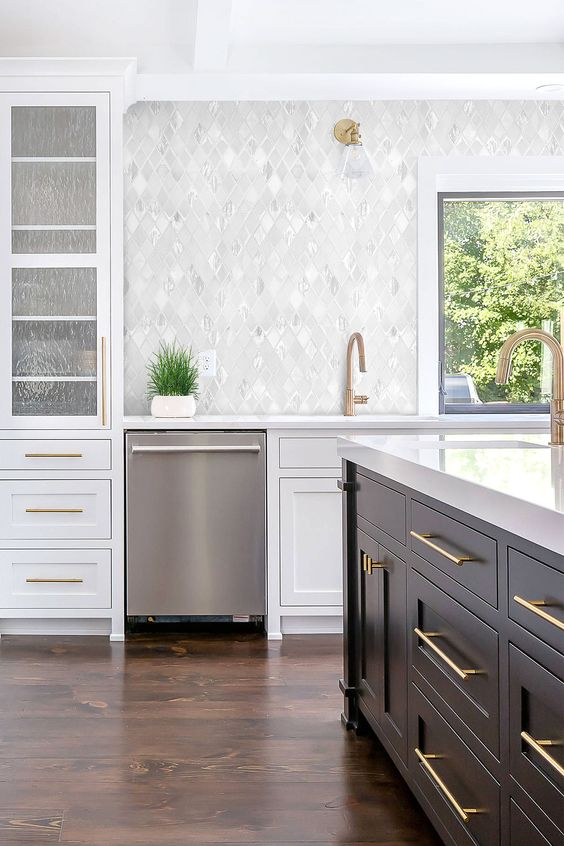 a chic kitchen with white cabinetry, a black kitchen island, white quartz countertops, a pretty marble tile backsplash and brass fixtures