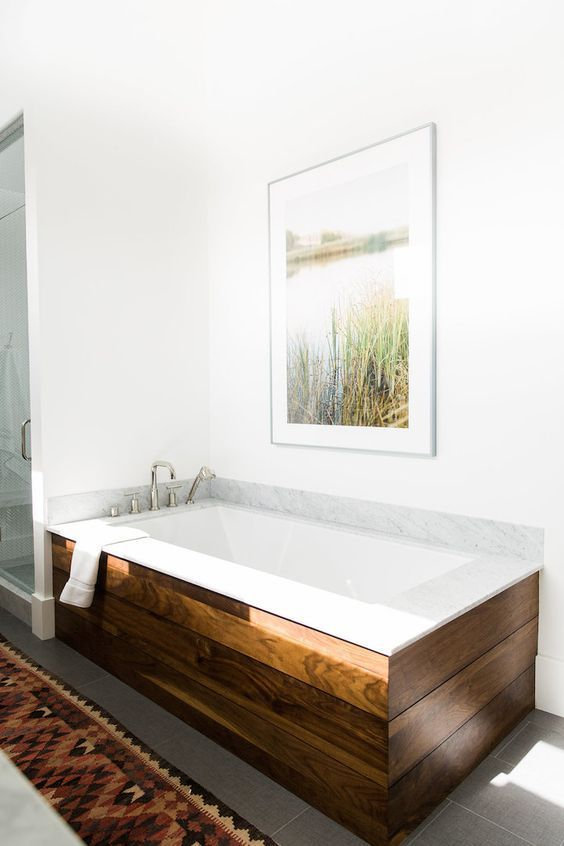 a chic mid-century modern bathroom in neutrals, with a tub clad with rich-stained wood and an artwork