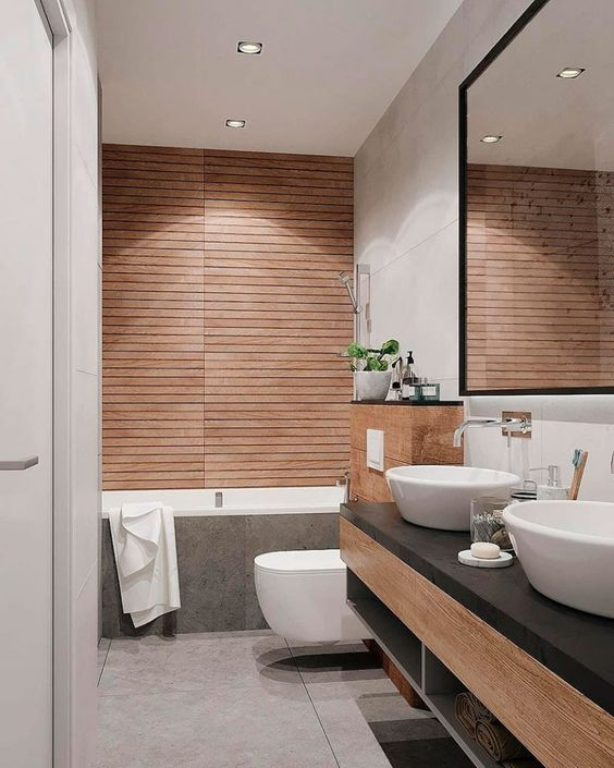 a chic minimalist bathroom with a wood clad wall, wooden tiles and a wooden vanity plus a statement mirror