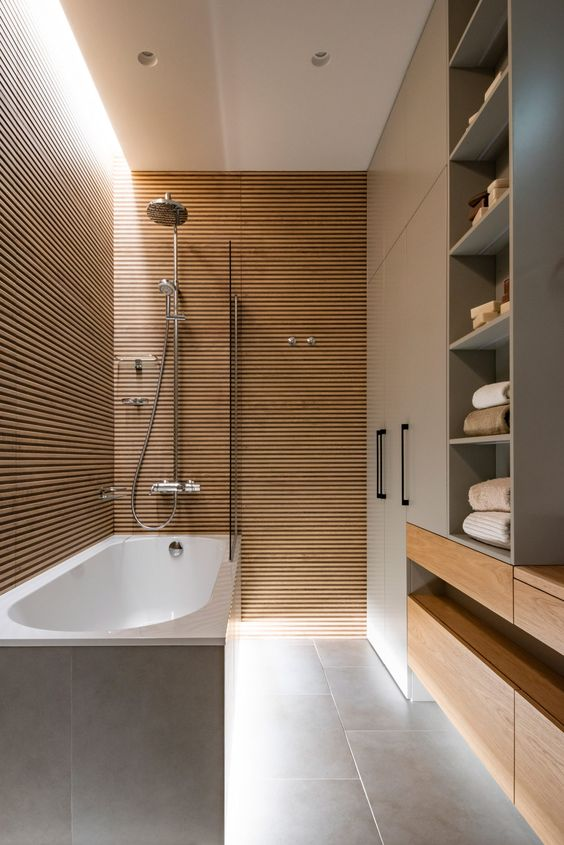 a chic minimalist bathroom with walls clad with wood slabs, a large storage unit with wooden drawers is wow