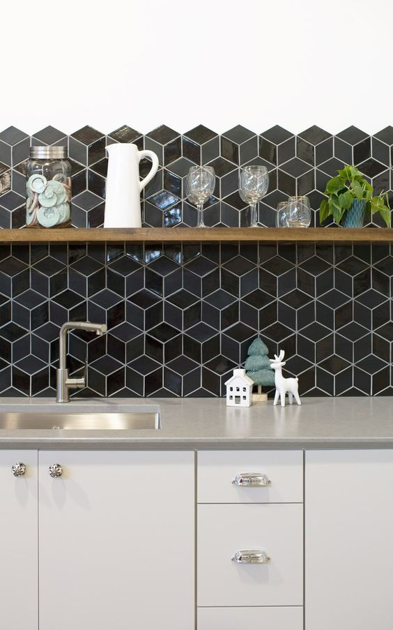 a chic off-white kitchen with grey countertops and glossy black geometric tiles on the backsplash is amazing