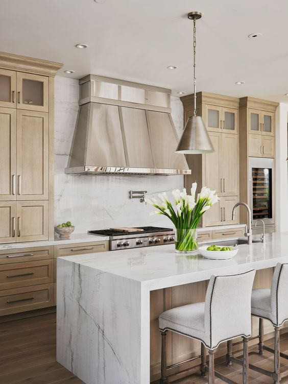 a chic tan kitchen with white quartz countertops and a backsplash, a metal hood and pendant lamps plus comfy stools
