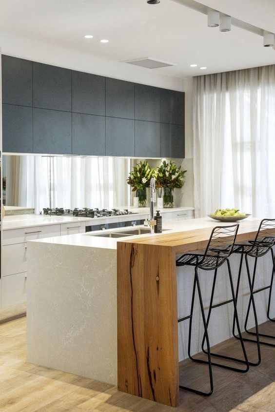 a chic two tone kitchen in black and white, with a large kitchen island that features an additional wooden waterfall countertop for eating