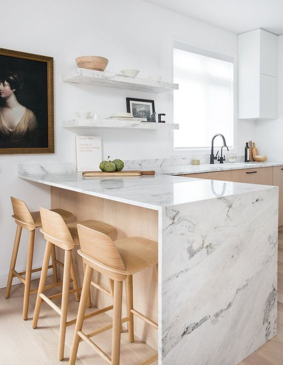a chic two tone kitchen with white stone countertops including a waterfall one plus open shelves and cabinets
