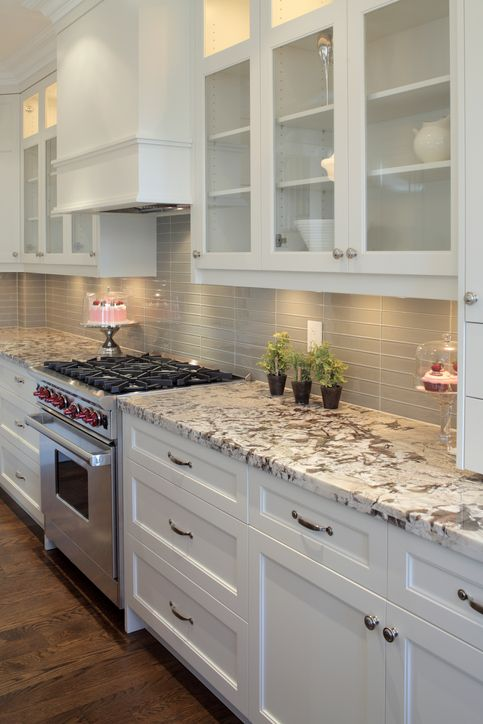 a chic white kitchen with a grey skinny tile backsplash, grey granite countertops and stainless steel appliances is amazing