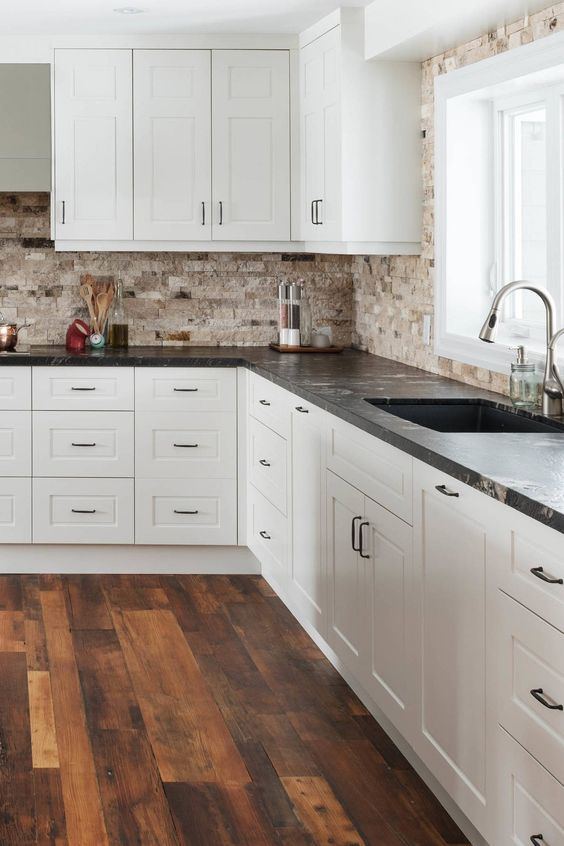 a chic white kitchen with a tan stone tile backsplash and black granite countertops plus black handles is a stylish space