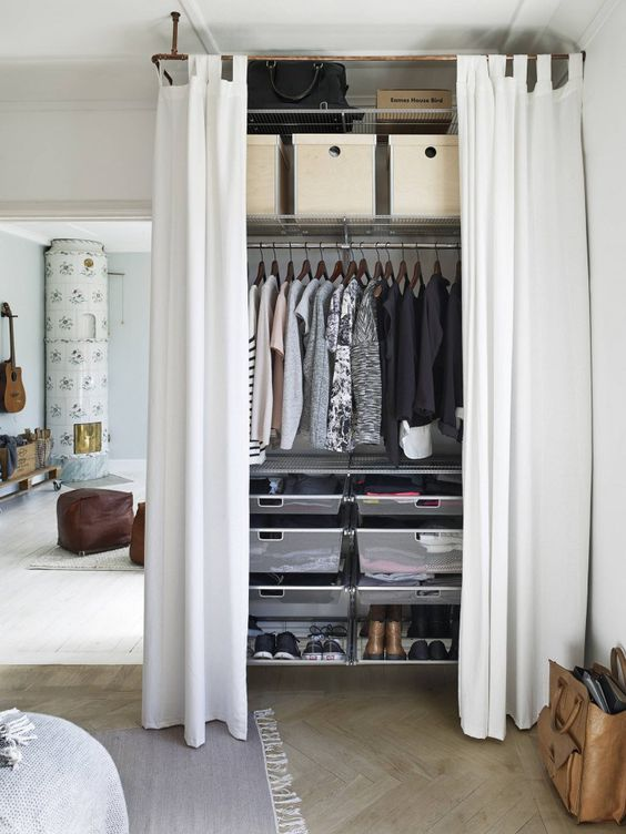 a closet with sheer drawers and shoe shelves, a makeshift closet and shelves for bags and boxes for storage