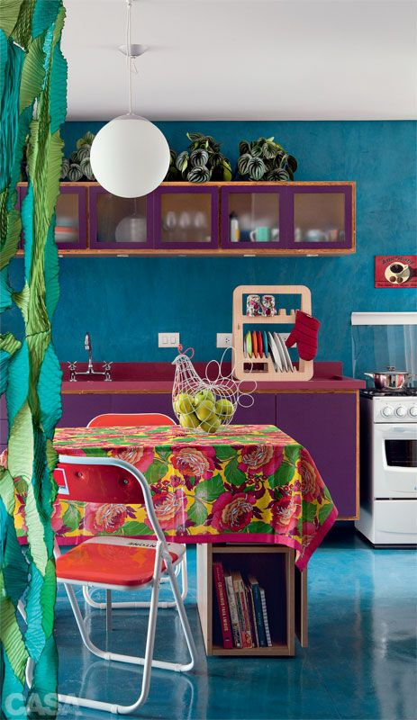 a colorful kitchen with blue walls, purple cabinets, a pink countertop and colorful chairs and linens