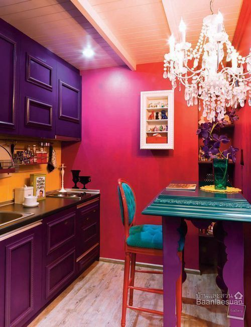 a colorful kitchen with pink and red walls, purple cabinets, black coutnertops and a yellow backsplash, a green table and a crystal chandelier