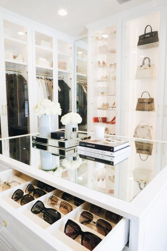 a comfortable white closet with lit up shelves and glass doors, with space for every type of clothes and shoes and a dresser for accessories