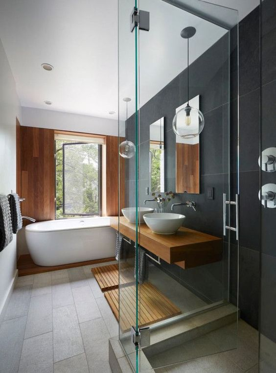 a contemporary bathroom clad with large scale tiles, with a wooden wall, a platform and mats plus a floating vanity