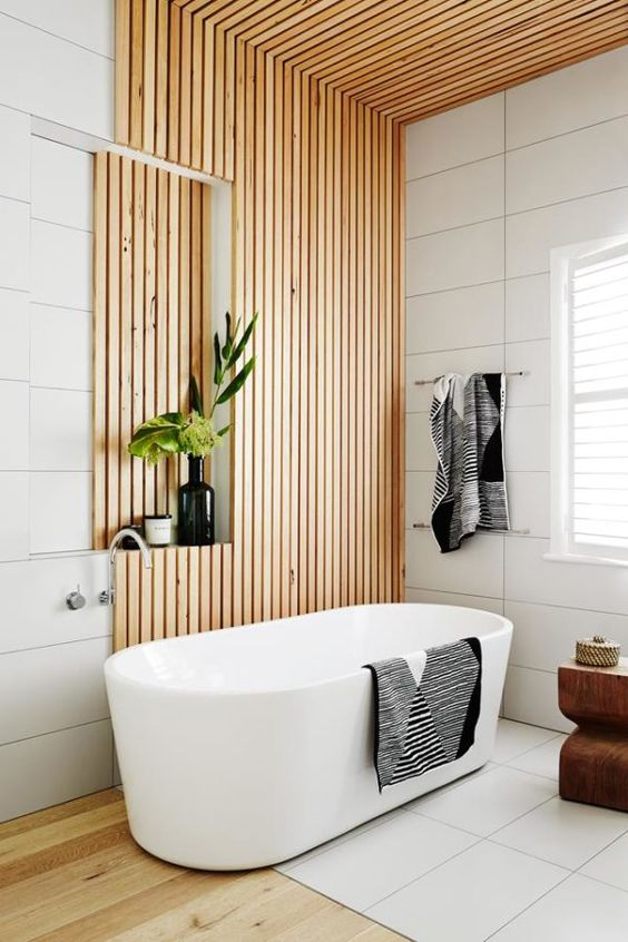 a contemporary bathroom clad with white tiles and with wooden slabs covering the wall and ceiling