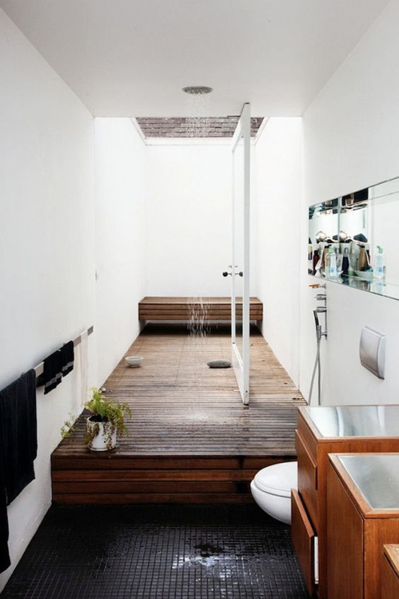 a contemporary bathroom in neutrals, with a black tile floor and a shower space done with wood is super cool