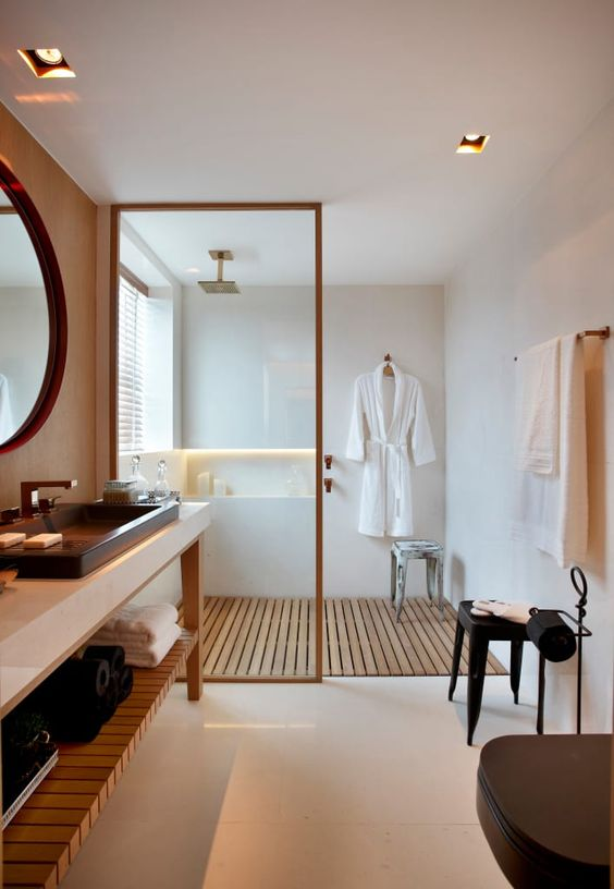 a contemporary bathroom in neutrals, with a wooden floor in the shower and a vanity with a wooden shelf
