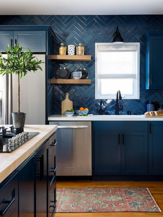 a contemporary blue kitchen with white quartz countertops, a matching blue herringbone backsplash and touches of black here and there