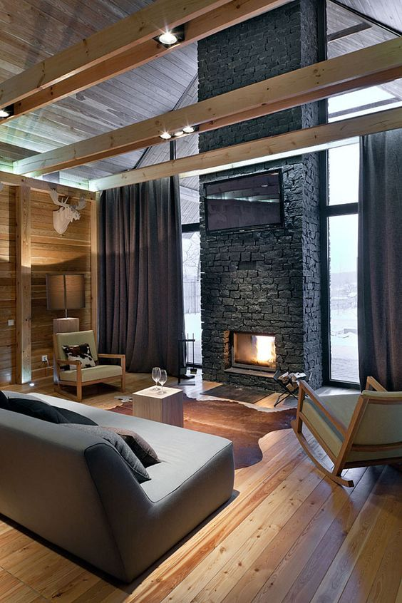 a contemporary chalet living room all clad with wood, with a faux stone fireplace, modern and minimalist furniture and wooden beams
