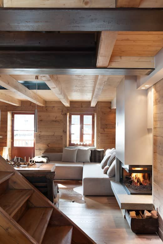 a contemporary chalet living room clad with wood, with a modern fireplace and some firewood stored