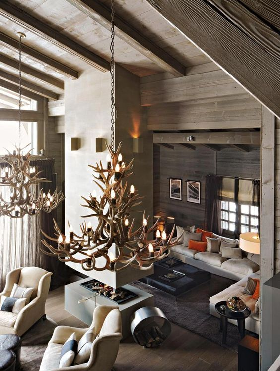 a contemporary chalet living room with a concrete fireplace, neutral furniture, antler chandeliers and colorful pillows