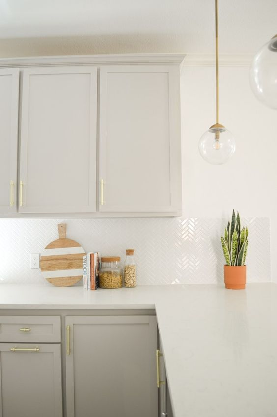 a contemporary dove grey kitchen with a white herringbone tile backsplash and white quartz countertops, glass pendant lamps and potted plants