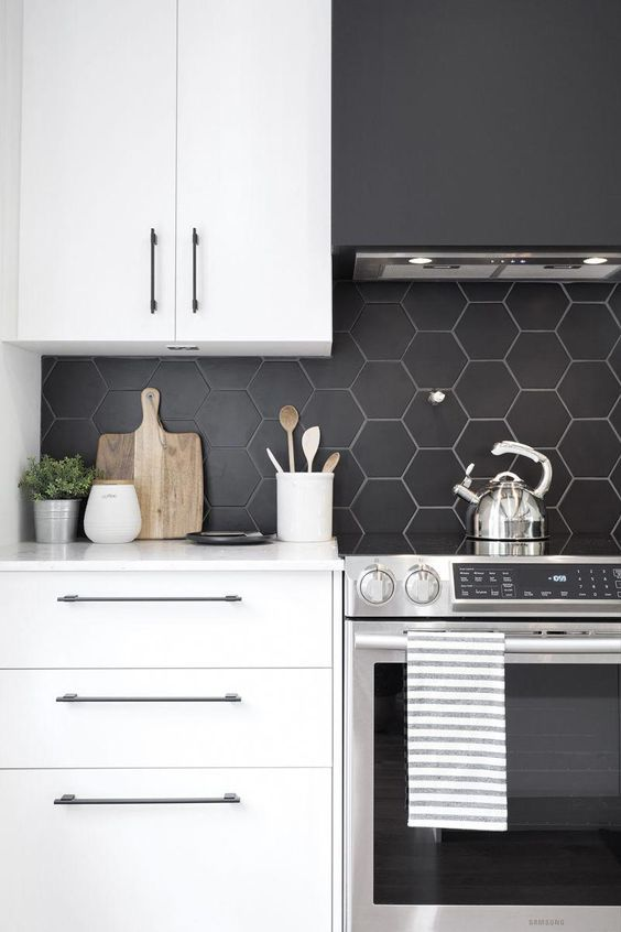 a contemporary kitchen with white cabinetry, a black matte hexagon tile backsplash and a black hood looks contrasting