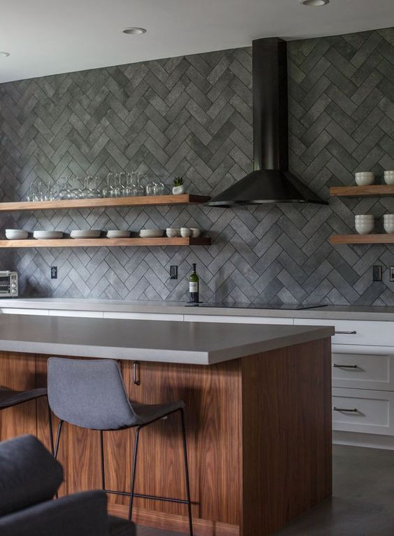 a contemporary kitchen with white cabinets, a stained kitchen island and grey stone countertops plus a herringbone concrete backsplash