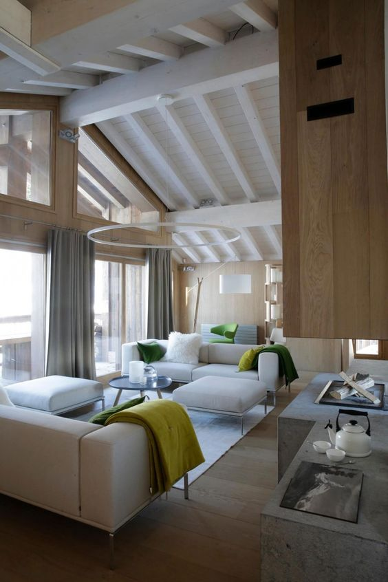 a contemporary light-filled chalet living room with neutral furniture, a glazed wall and an open fireplace of concrete