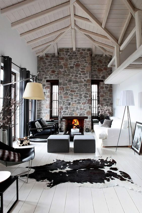 a contemporary living room with white walls, a whitewashed wooden ceiling, a stone clad fireplace and cool furniture