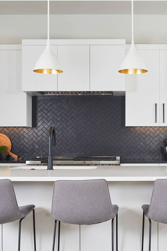 a contemporary white kithen with a black herringbone backsplash, tall grey stools and pendant lamps with gold inner
