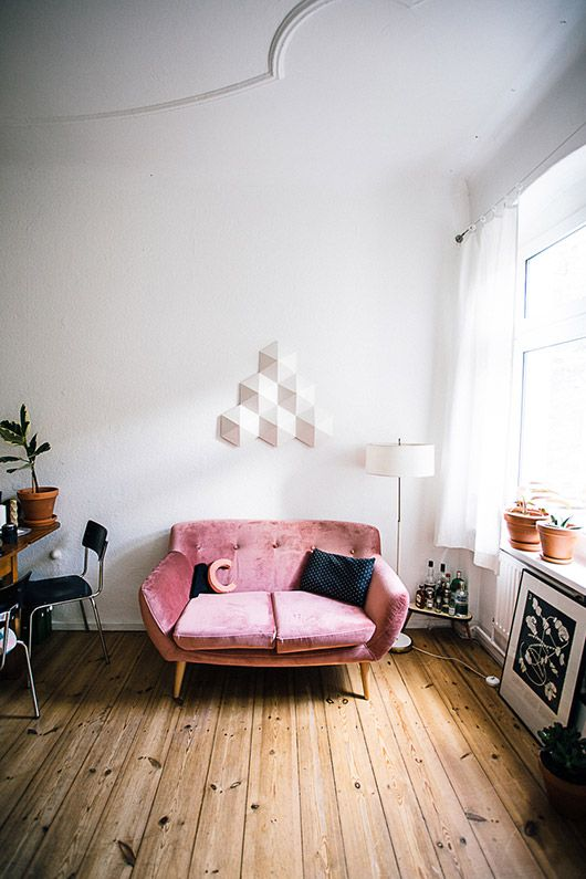 a cool contemporary space with a pink loveseat, pretty art, potted plants and blooms is a chic and welcoming room