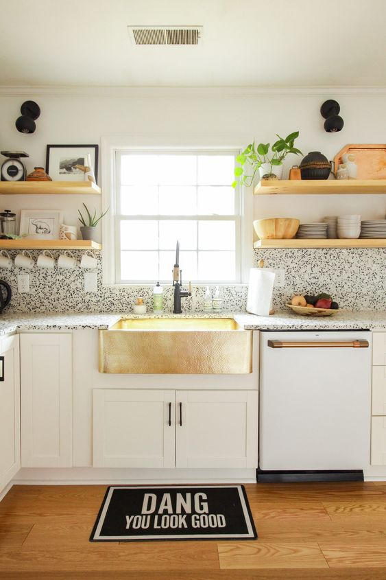 a cool white modern kitchen with black and white terrazzo countertops and a backsplash plus touches of gold