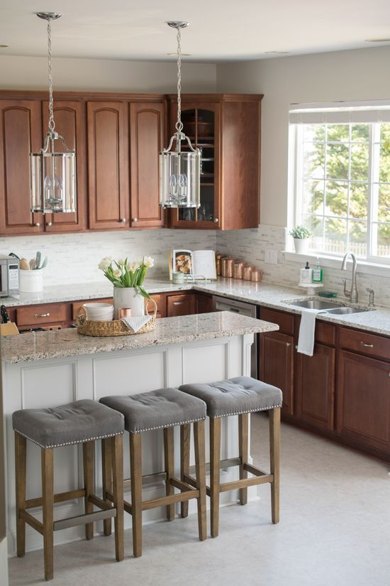 a copper-colored kitchen in vintage style, with a white tile backsplash and creamy granite countertops plus pendant glass lamps on chains