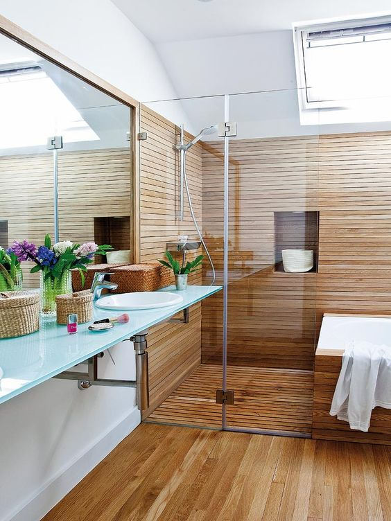 a cozy bathroom clad with wood, with a floating vanity and a skylight is super welcoming and inviting