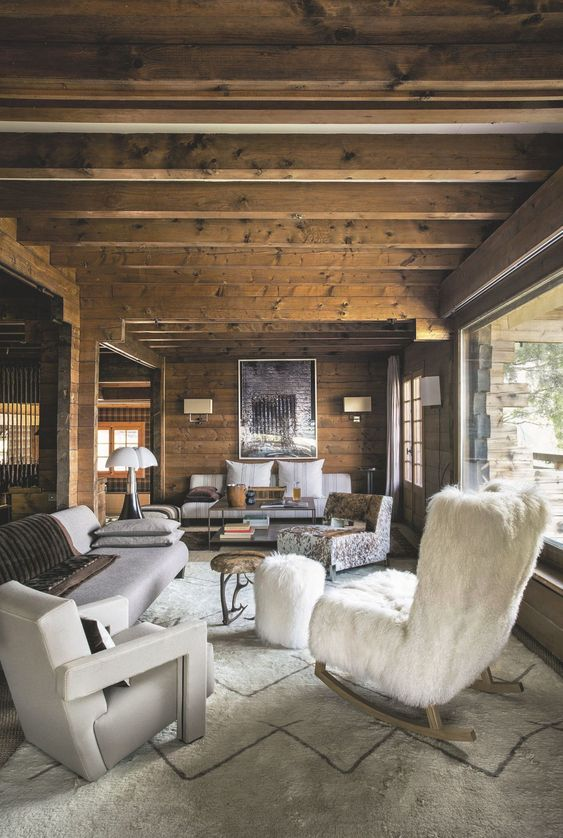 a cozy chalet living room with a wooden ceiling with beams and a glazed wall, stylish and refined furniture and elegant lamps