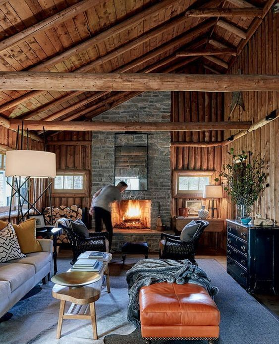 a cozy chalet living room with all wood around, a stone fireplace, a leather ottoman, firewood storage and chic furniture