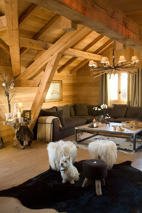 a cozy chalet living room with wooden walls and a ceiling, a rustic chandelier, a black sectional, a black rug, fluffy stools