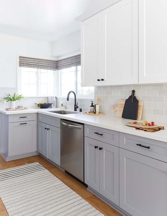 a cozy farmhouse kitchen with white and grey cabinets, a grey tile backsplash and white quartz countertops is chic