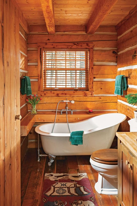 a cozy log cabin bathroom fully clad with wood, with wooden frames and a vanity is a veyr lovely space