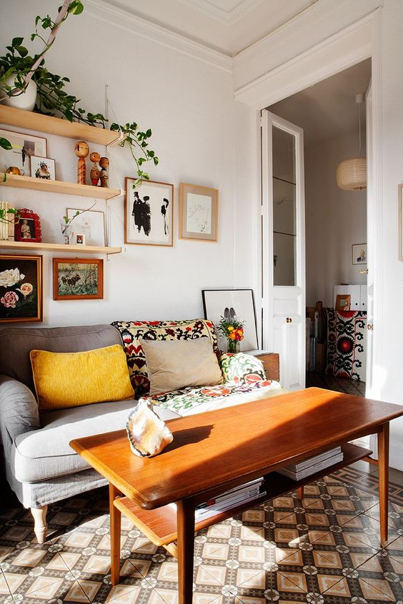 a cozy modern nook with open shelves, a grey loveseat with bright upholstery, a mid-century modern table and a tiled floor