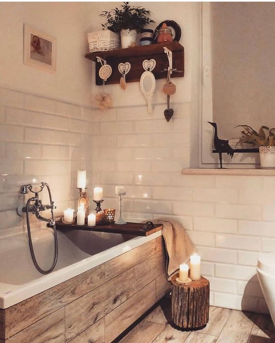a cozy white bathroom with a tub clad with wood tiles and a matching floor looks very cute and cool
