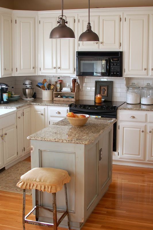 a creamy vintage kitchen with granite countertops, metal pendant lamps and metal stools looks cozy and stylish