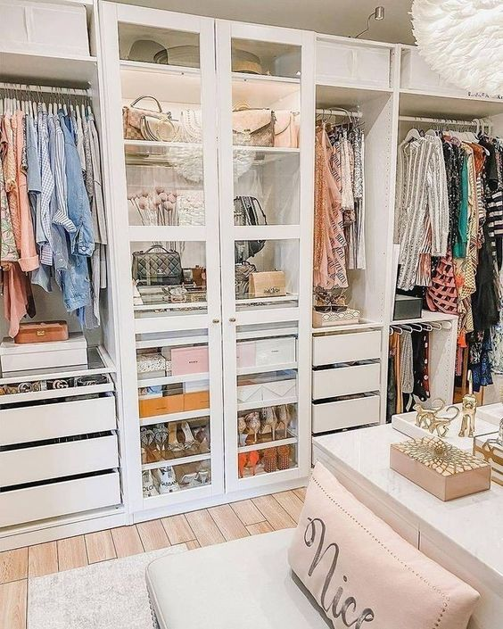 a cute white closet with drawers, boxes, open storage compartments, a wardrobe with glass doors that is lit up