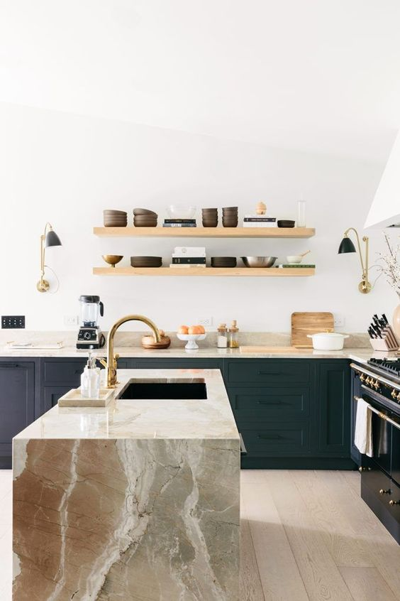 a dark green kitchen in modern farmhouse style, with a beautiful tan stone waterfall countertop that adds chic to the space