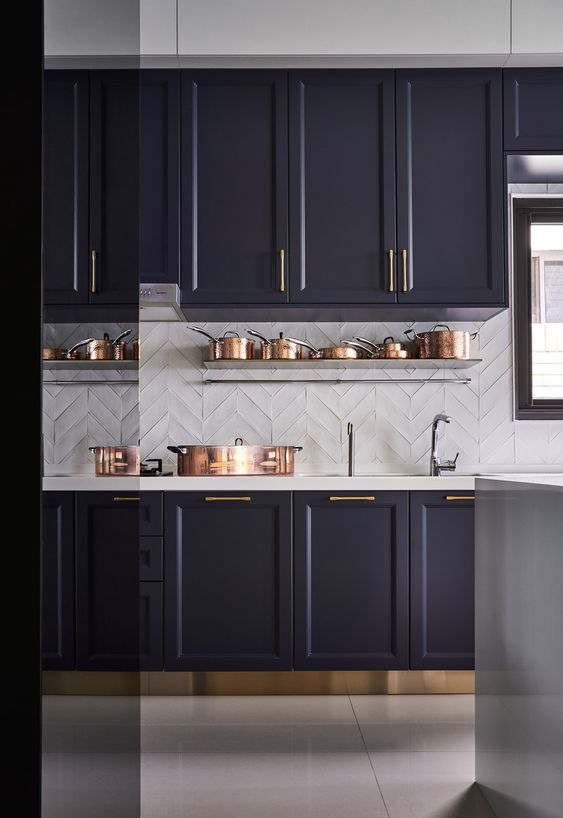 a dark purple kitchen in vintage style, a white tile backsplash and coutnertops plus brass and copper touches