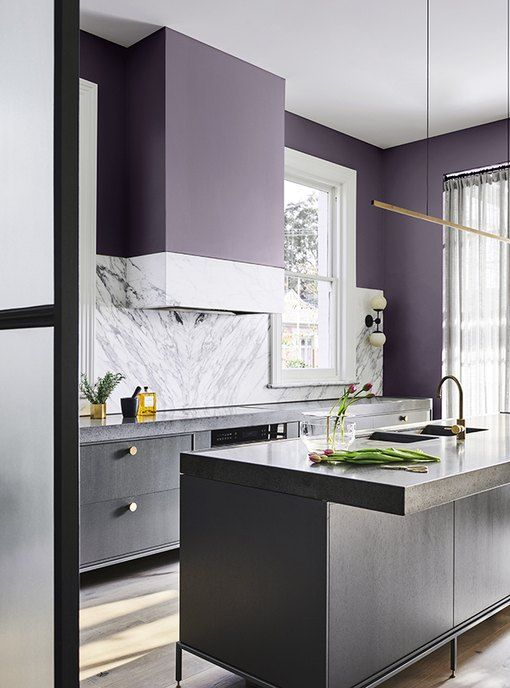 a dark purple kitchen with grey cabinetry and white stone countertops and a backsplash plus touches of gold