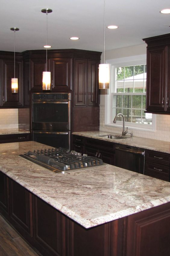 a dark stained kitchen with white and brown granite countertops and a white tile backsplash that refresh this dark and chic space